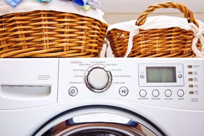 close up of buttons on a front load washing machine with baskets of laundry sitting on top