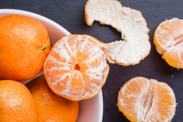 bowl of oranges with one orange partial peeled showing white pith