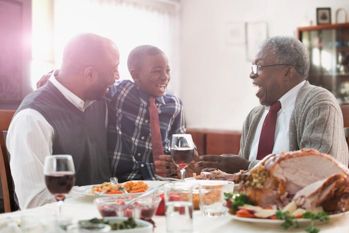 family laughing and talking at thanksgiving dinner