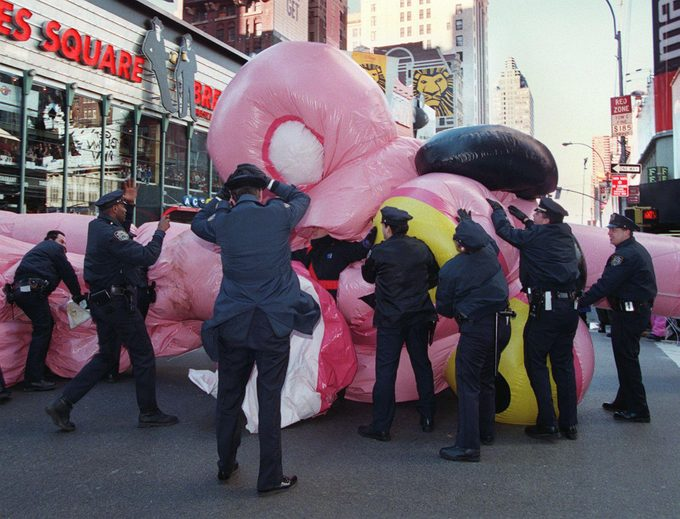 New York City Police rush to the aid of the Pink Panther balloon as it collapses after being blown over due to high winds 27 November at the 71st annual Macy's Thanksgiving day parade in New York.