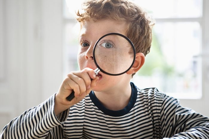 boy playing live clue with magnifying glass