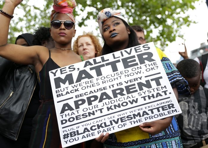 """Two women hold a placard with the slogan """"Yes, all lives matter"""" as people gather in protest"""
