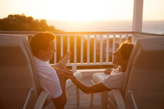 Couple on a romantic getaway vacation smiling with each other while watching the sunset at a resort