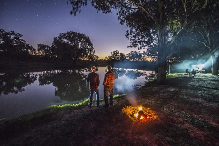 Two men stand by a campfire and watch the stars