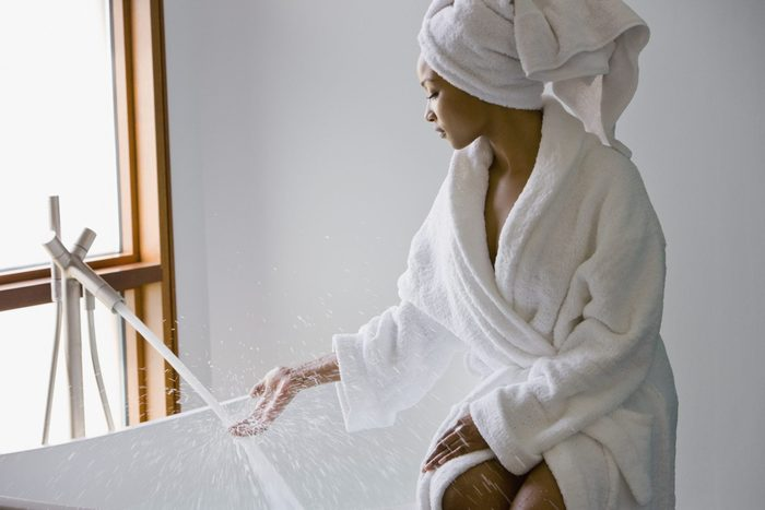 young woman wearing a bath robe filling the bath tub up with water for a spa day