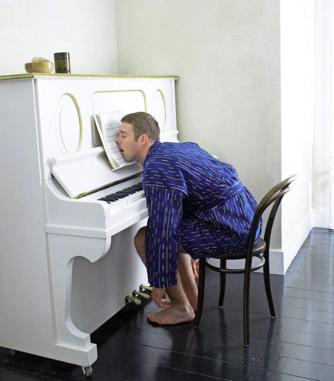 Young Man Wearing a robe asleep at the piano with his head on the sheet music