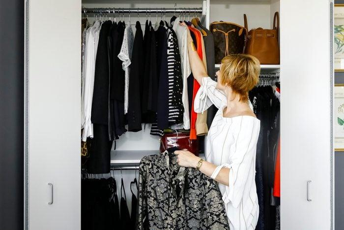 Caucasian woman hanging clothes in closet
