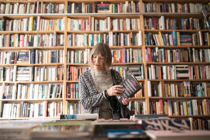 Senior woman with book standing against bookshelf in a book store