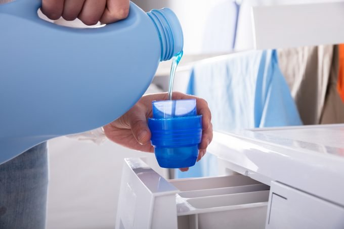 Person Pouring Detergent In Lid