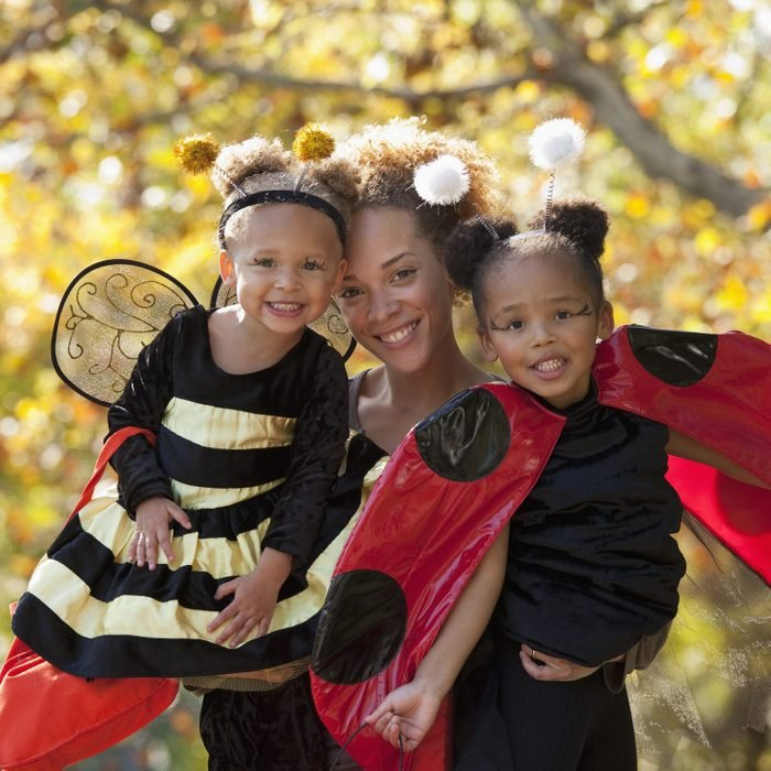 mother smiling with her two daughters dressed up as a bumble bee and a lady bug for halloween