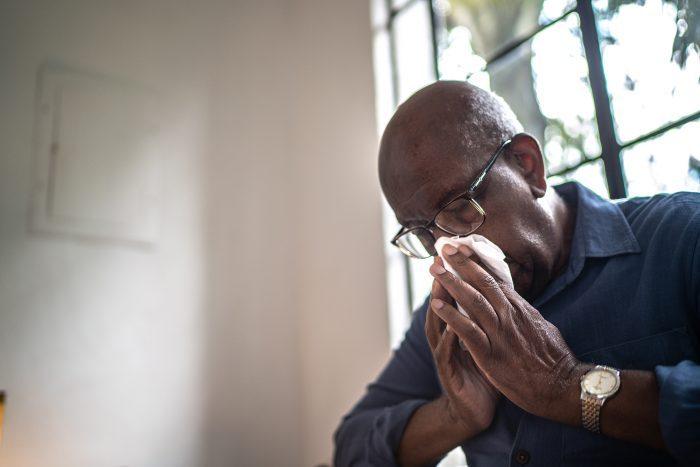 Senior Man Sneezing At Home