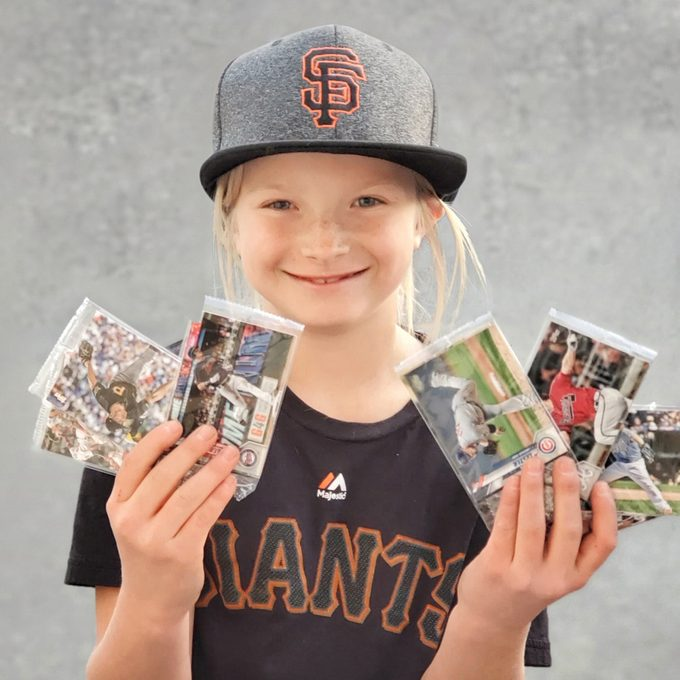 little girl wearing San Francisco baseball hat and shirt showing off a collection of baseball cards.