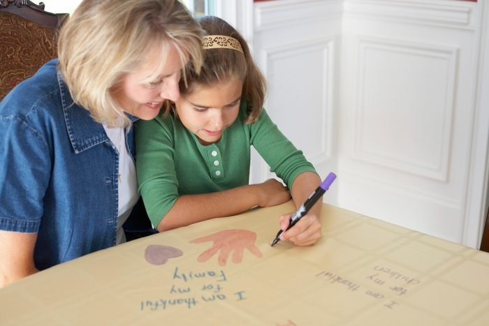 family creating a keepsake tablecloth on thanksgiving
