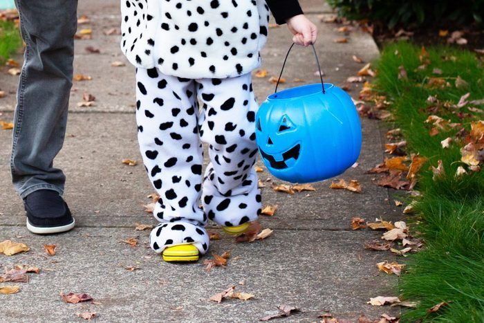 close up of anonymous child in a halloween costume holding a blue pumpkin candy bucket