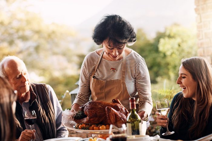 woman bringing the thanksgiving turkey to the dinner table