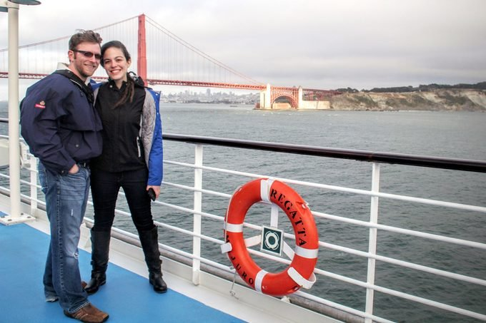 Billy Hirsch and girlfriend on the deck of a Regatta cruiseship passing by the Golden Gate Bridge in San Francisco, California in the background