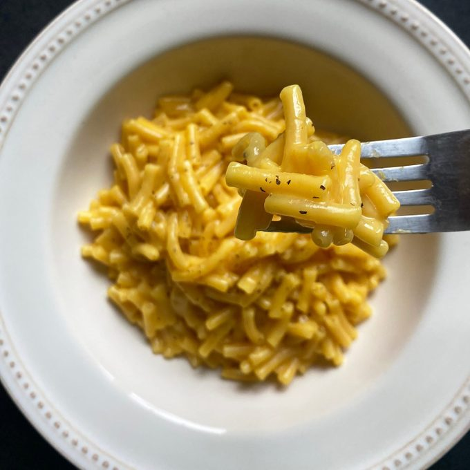 Tik Tok Mac And Cheese on the end of a fork in the foreground, in a white bowl in the background