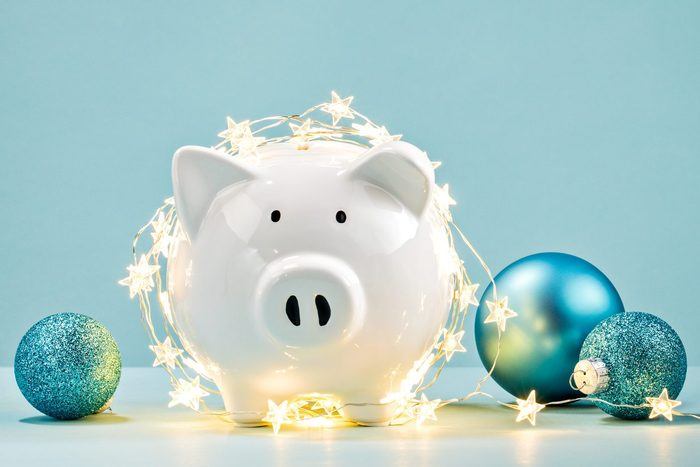 white Piggy bank wrapped in a string of Christmas lights on blue background