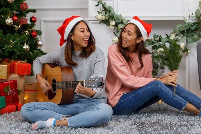 two sisters singing christian christmas carols around the christmas tree