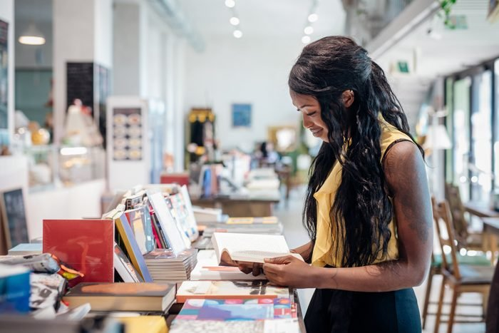 Young woman shopping for books in bookshop