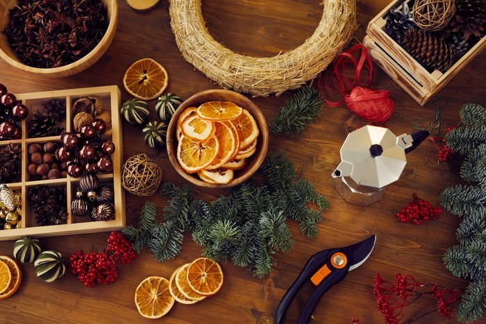 High angle view of beautiful toys and fir tree twigs for making Christmas wreath placed on wooden table with secateurs and coffeemaker