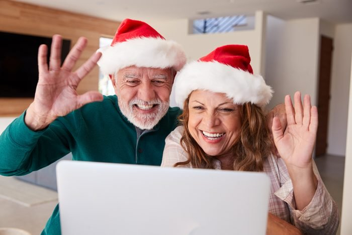 Senior Hispanic Couple Wearing Santa Hats With Laptop Having Video Chat With Family At Christmas