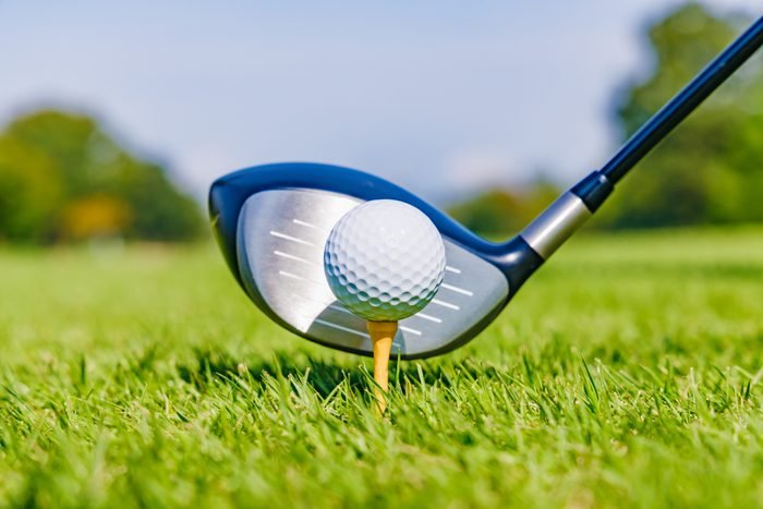 close up of golf ball on a tee in the grass with a club head behind it on a sunny day on a golf course