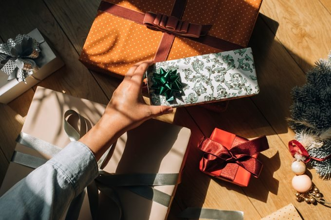 woman's hand putting together christmas gifts