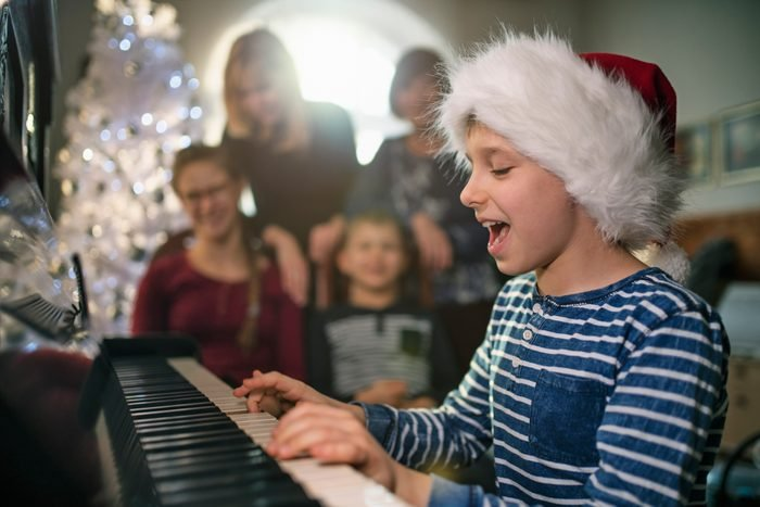 Little boy playing and singing carols on Christmas