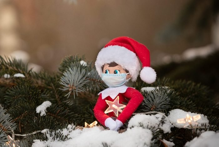 The Christmas toy sits on the branches of a snowy tree in an embrace with a sparkling star. Coronavirus Covid Christmas: a toy doll wearing a real medical mask. Social distancing during a pandemic