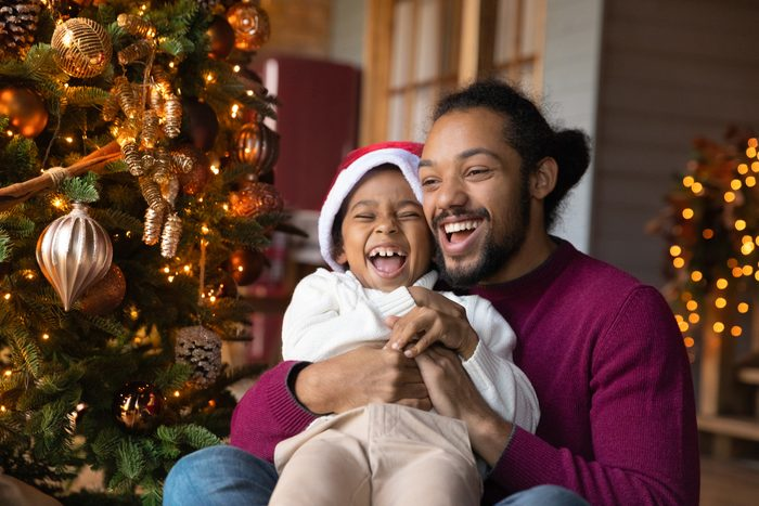 Excited biracial father and son play near fir tree