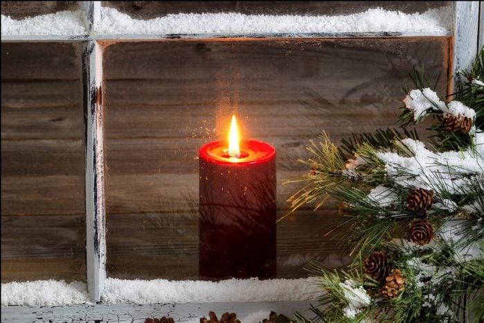 Tea Light Candle Seen Through Glass Window During Winter