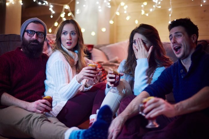 friends watching a holiday movie while playing a drinking game
