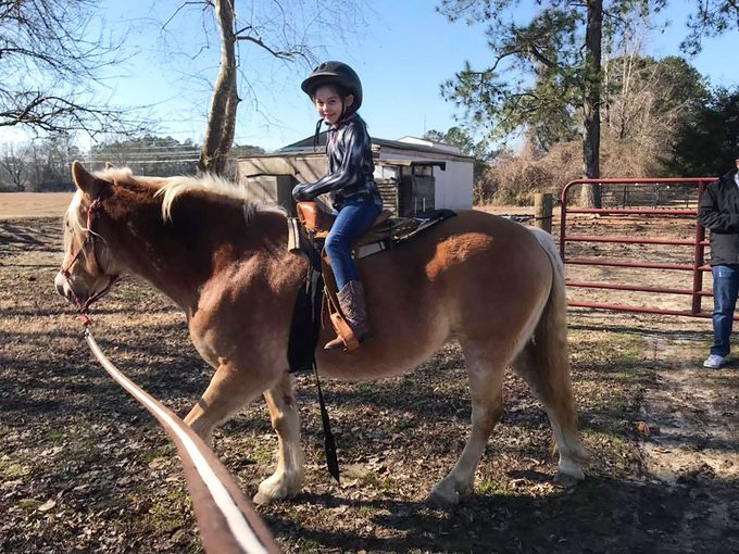 Little girl riding on a horse.