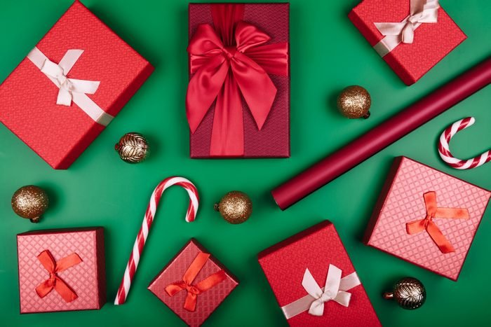 Christmas background with gift boxes, clews of rope, paper's rools and decorations on red. Preparation for holidays. Top view with copy space.
