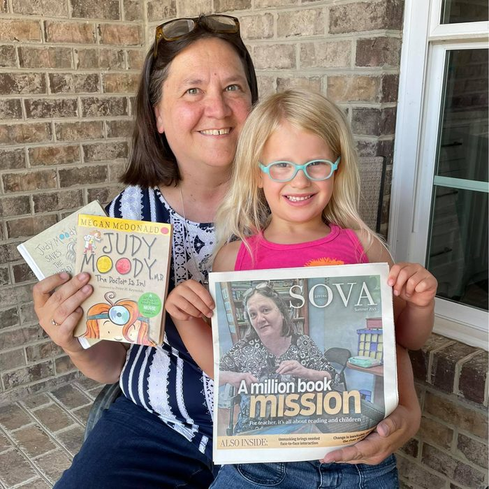 Jennifer Williams holding to books with her daughter sitting on her lap holding a newspaper celebrating William's mission