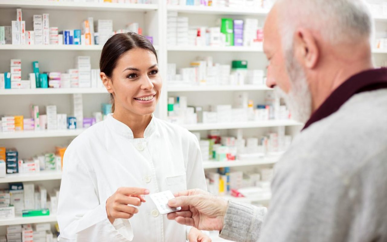 Beautiful,young,pharmacist,selling,medications,to,senior,patient