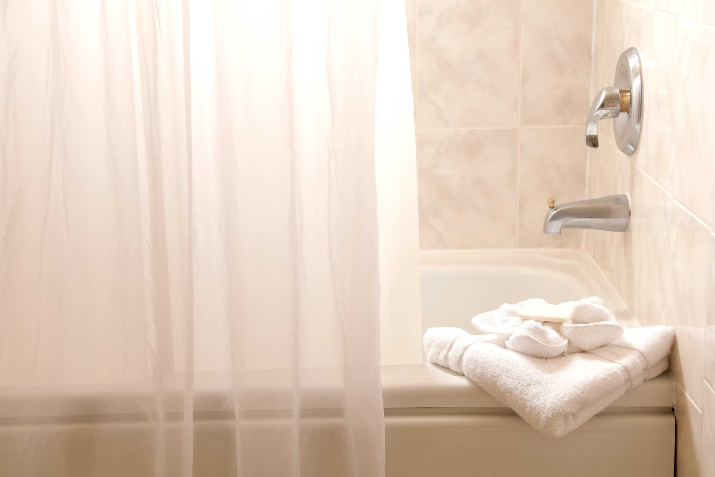 Wash the shower curtain in hot water and bleach every month