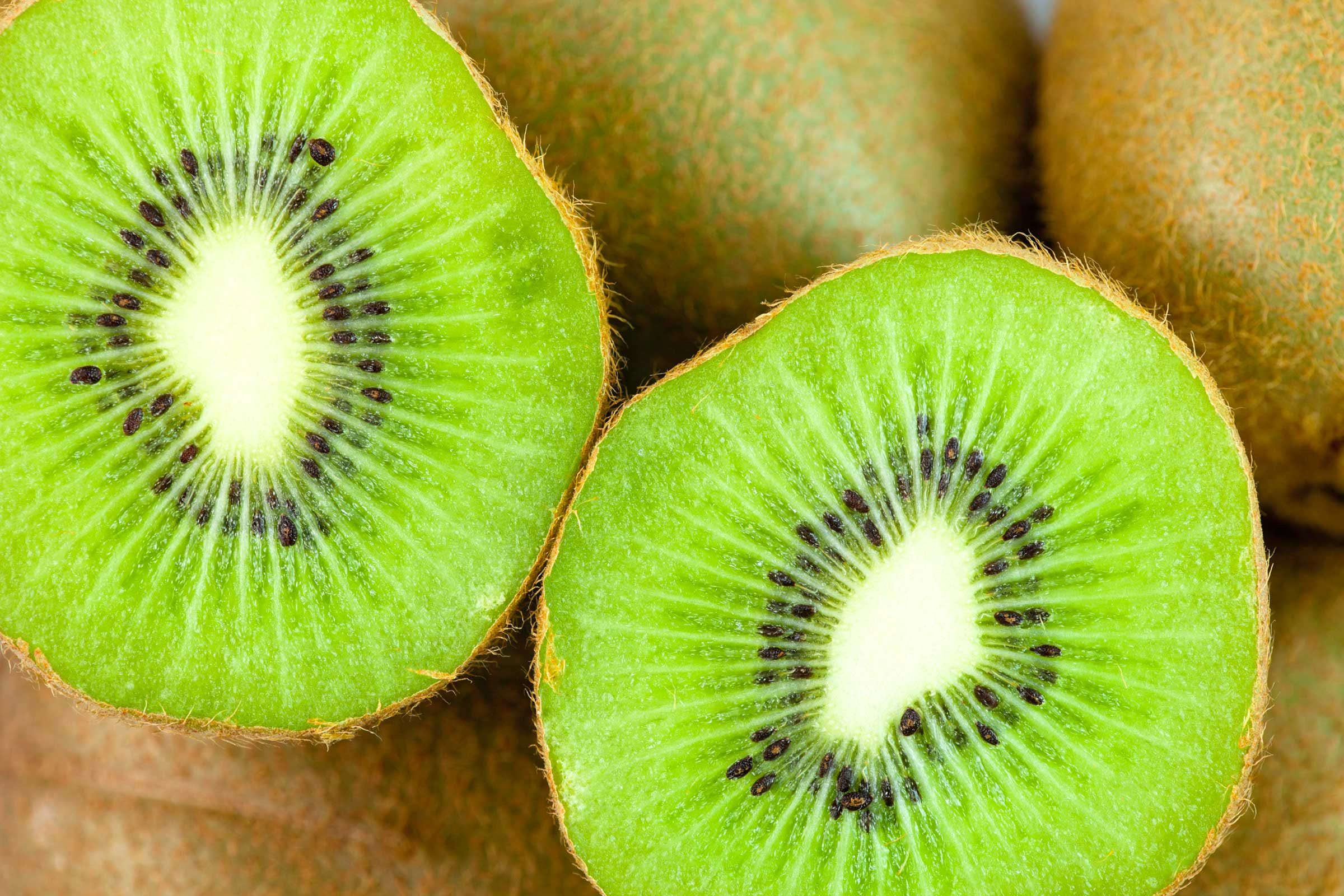 Cut a kiwifruit in half, then scoop out the flesh with a spoon